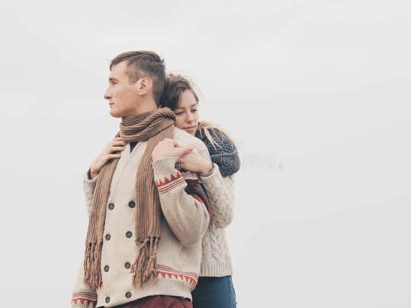 在被编织的毛线衣的年轻有吸引力的夫妇在海岸的峭壁 免版税图库摄影