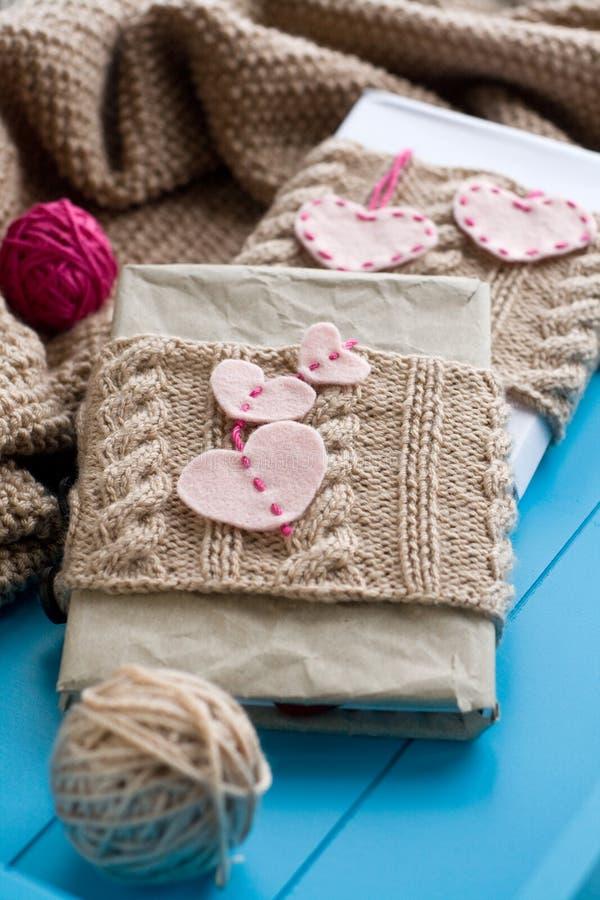 在被编织的盖子的两个老垫有毛毡心脏的 免版税库存照片
