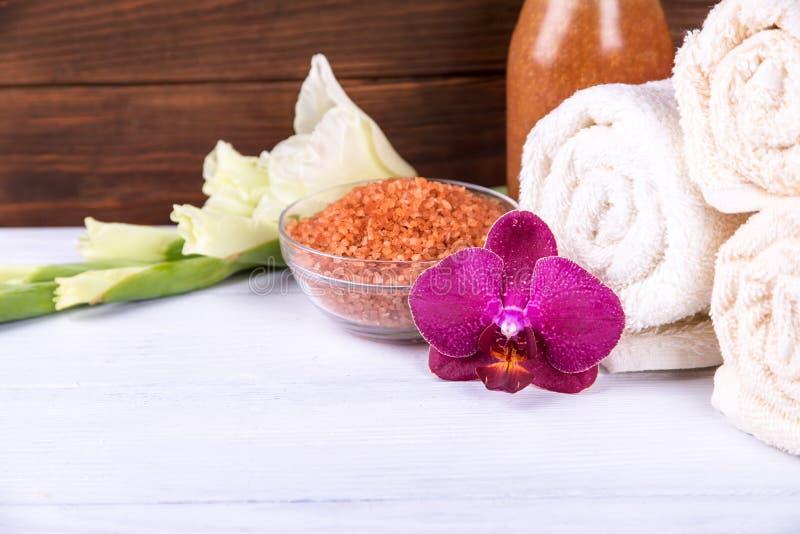 在被设置的温泉的接近的看法:海盐和兰花与毛巾和在背景洗刷在白色木桌上 中央焦点 免版税库存图片