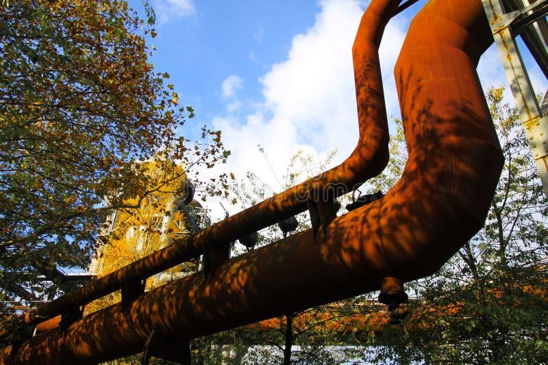 在被隔绝的弯曲的被腐蚀的管道的低角度视图反对天空蔚蓝和树 免版税库存图片