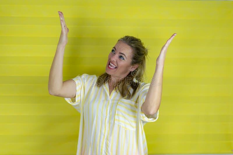 在被隔绝的背景的微笑年轻的美女显示两只手开放棕榈 免版税库存图片