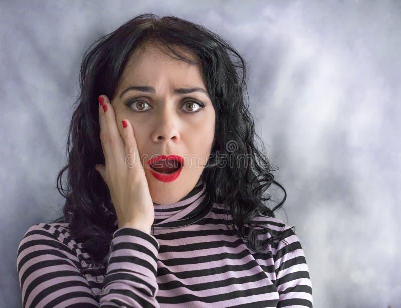 在被隔绝的背景的成人西班牙妇女害怕和冲击与惊奇表示 免版税库存照片