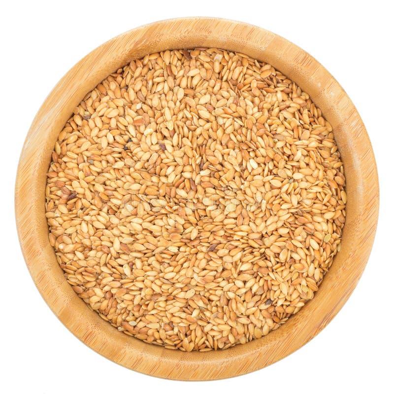在被隔绝的木碗的金黄亚麻籽 免版税库存照片