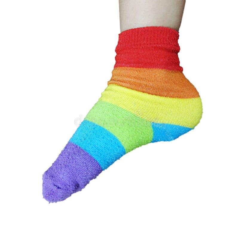 在被隔绝的脚的佩带的彩虹袜子 免版税库存照片