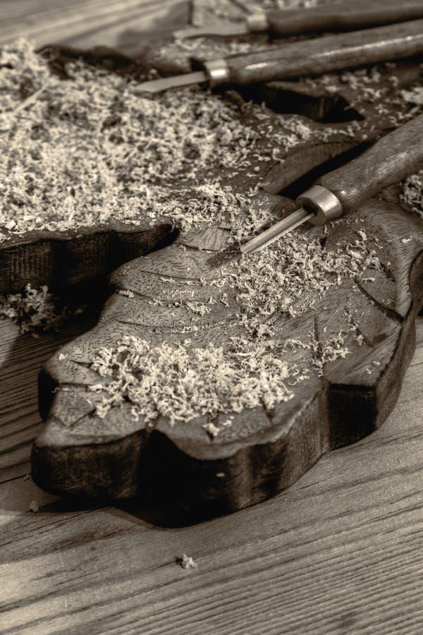 在被雕刻的木头块的凿子与削片的 库存照片