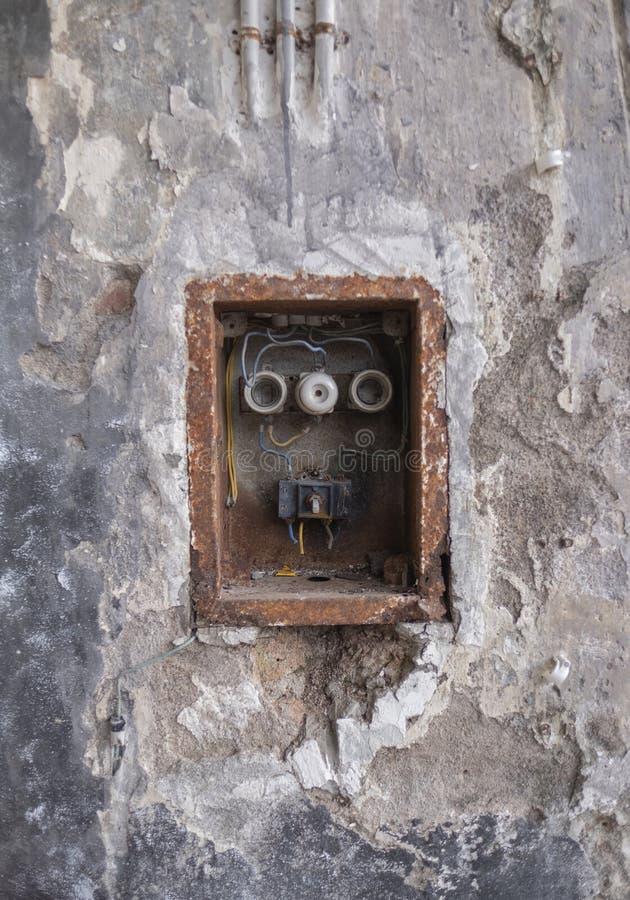 在被风化的墙壁上的老坏生锈的开关盒 库存照片