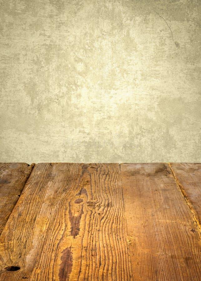 在被风化的墙壁前面的木桌 免版税库存照片