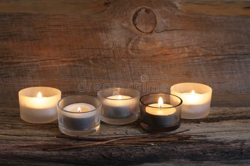 在被风化的木头的灼烧的蜡烛 库存图片