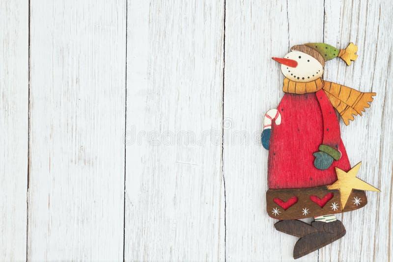 在被风化的白涂料织地不很细木头背景的一个雪人 免版税库存图片
