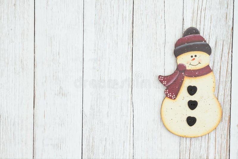 在被风化的白涂料织地不很细木头背景的一个雪人 库存图片