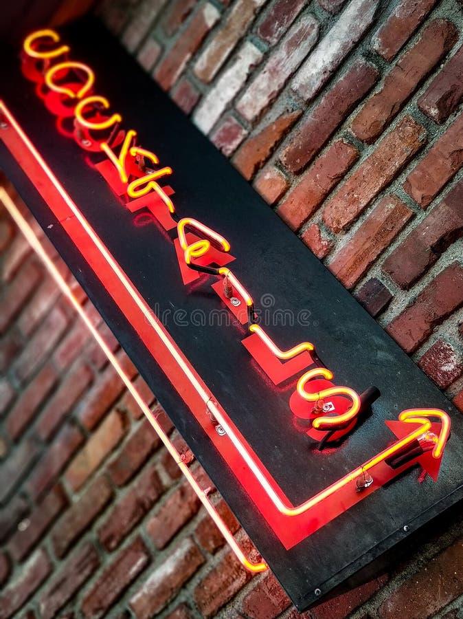 在被风化的砖的霓虹鸡尾酒标志 免版税库存照片