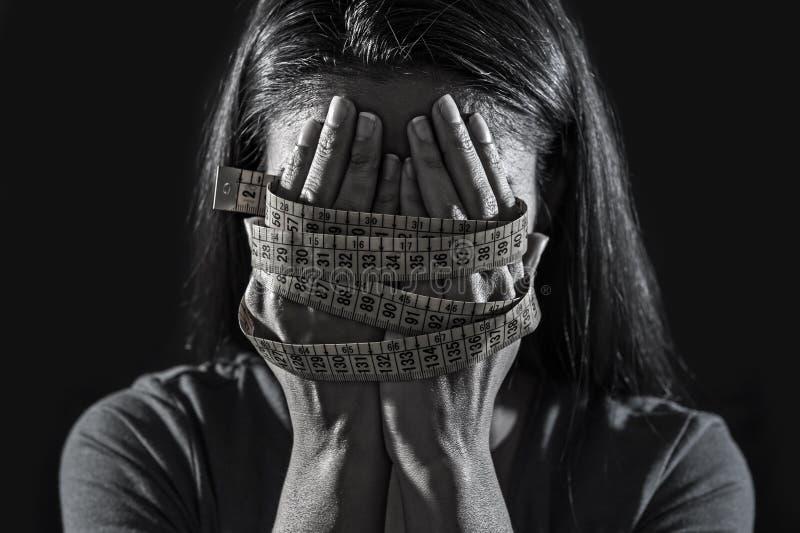 在裁缝措施磁带年轻人沮丧的和担心的女孩遭受的厌食或善饥癖营养dis的覆盖物面孔包裹的手 库存图片