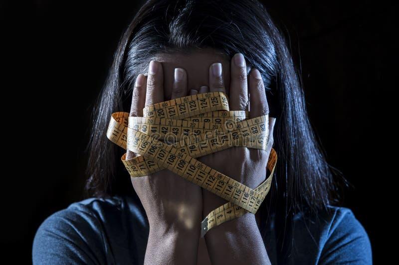 在裁缝措施磁带年轻人沮丧的和担心的女孩遭受的厌食或善饥癖营养dis的覆盖物面孔包裹的手 库存照片