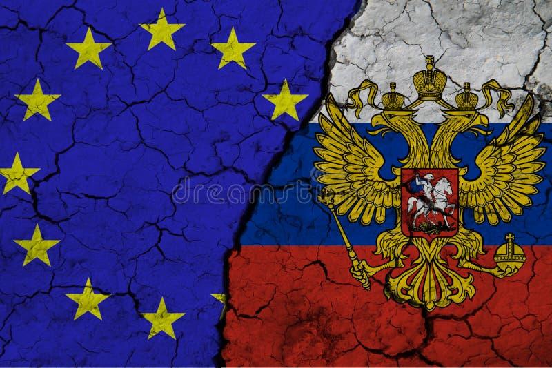 在裂土背景下近距离观察欧洲联盟旗帜和俄罗斯联邦国旗 的 免版税库存照片