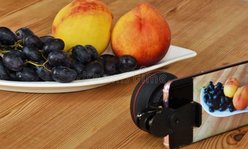 在装有桃子和黑葡萄的衣橱上放有宏镜的智能手机 免版税库存照片