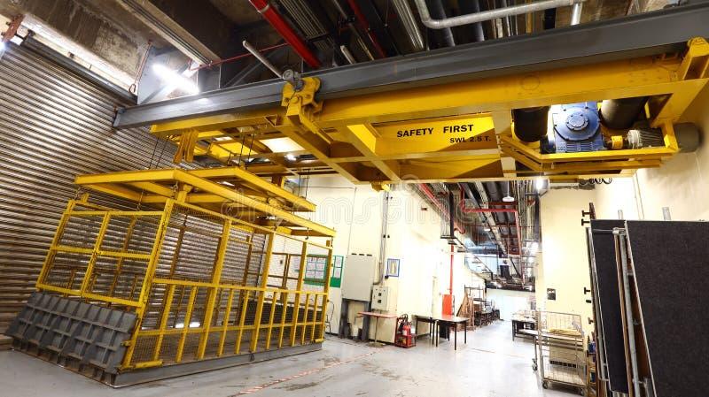 在装载在buil里面的重的机器的货架的黄色电梯 免版税库存图片