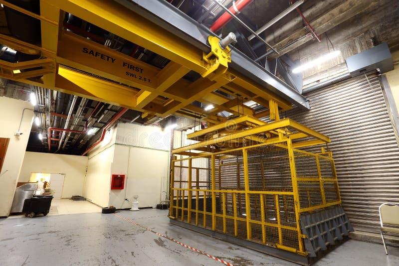 在装载在buil里面的重的机器的货架的黄色电梯 免版税图库摄影
