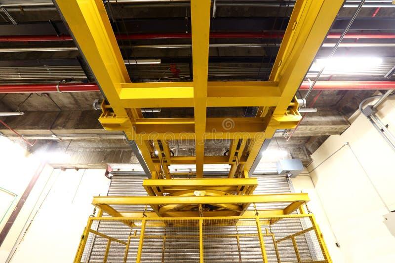 在装载在buil里面的重的机器的货架的黄色电梯 库存图片
