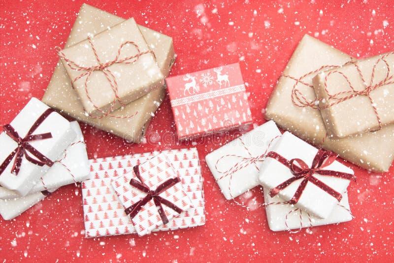 在装饰品纸和装饰红色绳索丝带包裹的圣诞节礼物红色表面上 创造性的爱好,顶视图 准备对Xmas 库存图片