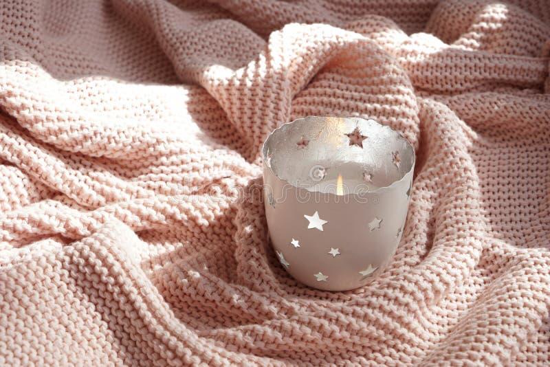 在装饰持有人的美好的灼烧的蜡烛在温暖的格子花呢披肩 免版税图库摄影