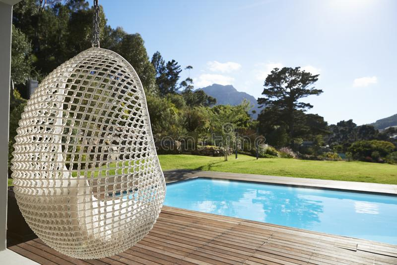 在装饰旁边的暂停的位子在室外游泳池附近 免版税库存照片