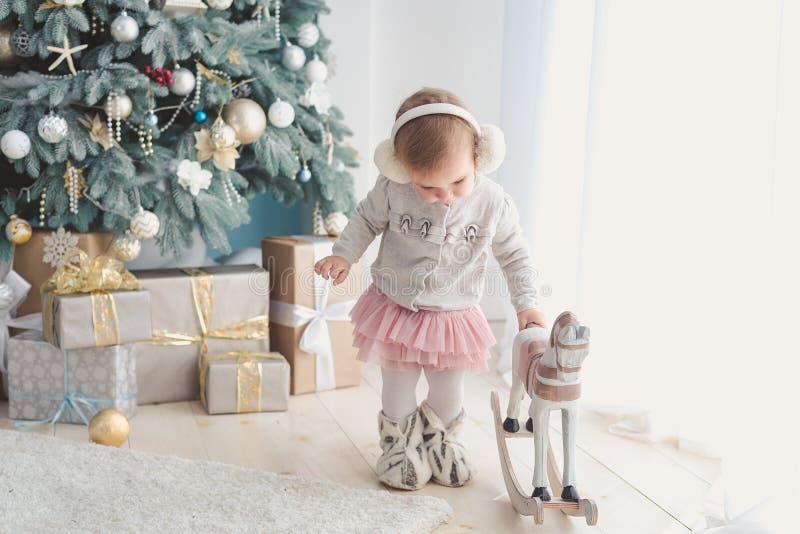 在装饰的圣诞树附近的美女与玩具木摇马 免版税库存图片