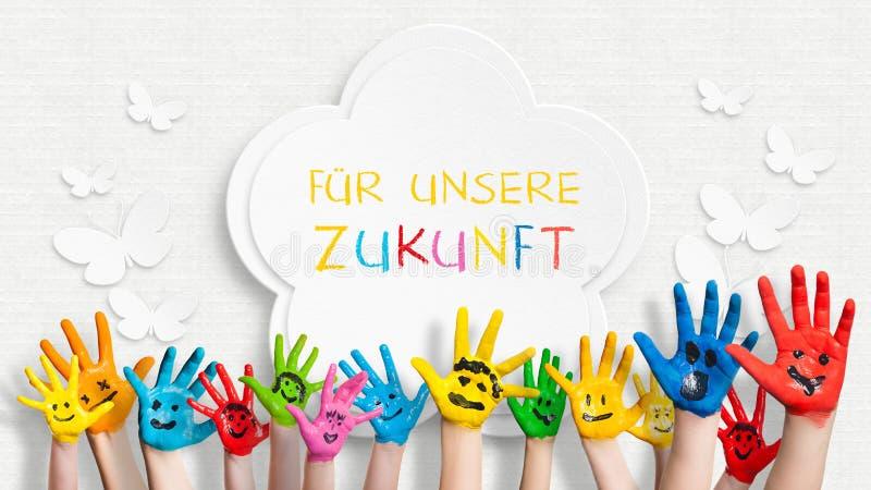 在装饰的墙壁前面的五颜六色的被绘的手有我们的未来的句子的用德语 免版税库存图片