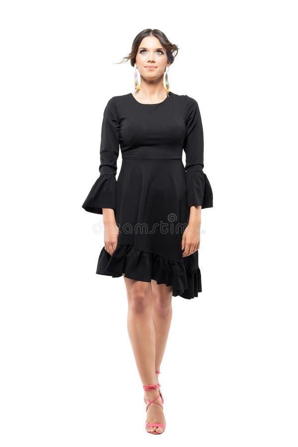 在装饰衣裙走与飞行头发和衣裳的黑色礼服的华美的拉丁秀丽 免版税图库摄影