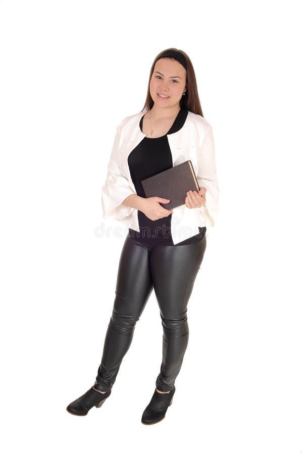 在裤子的十几岁的女孩身分在手上的拿着一本书 库存图片