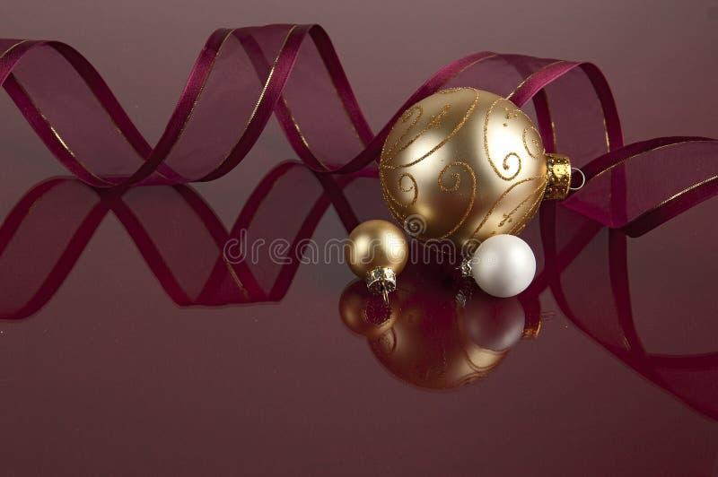 在褐紫红色的金和白色圣诞节球 免版税图库摄影