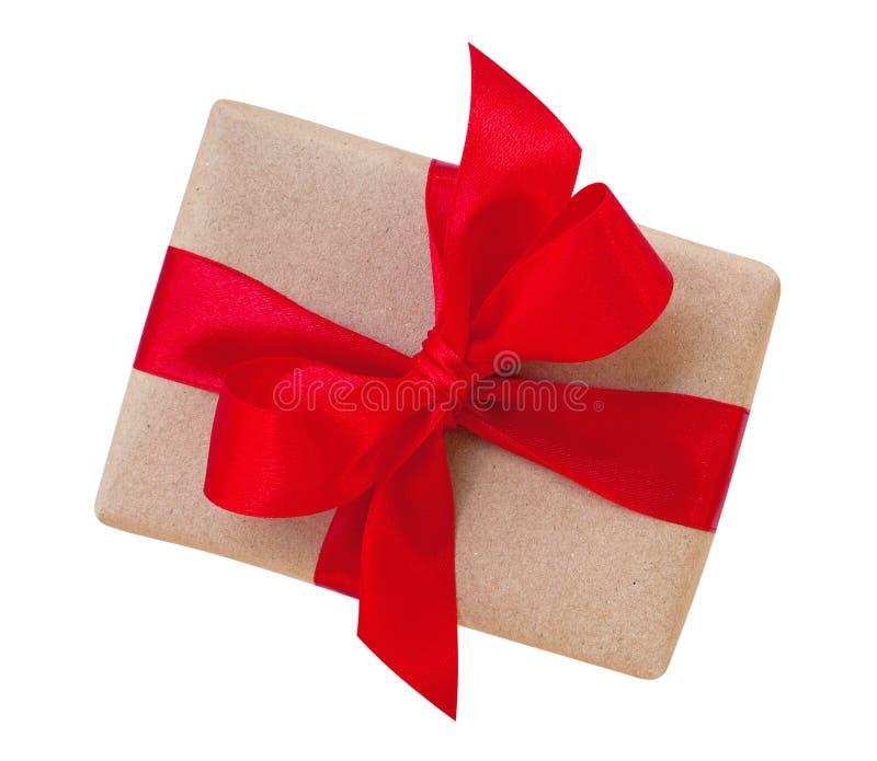 在褐色包裹的礼物盒回收了与红色丝带弓上面的纸 图库摄影