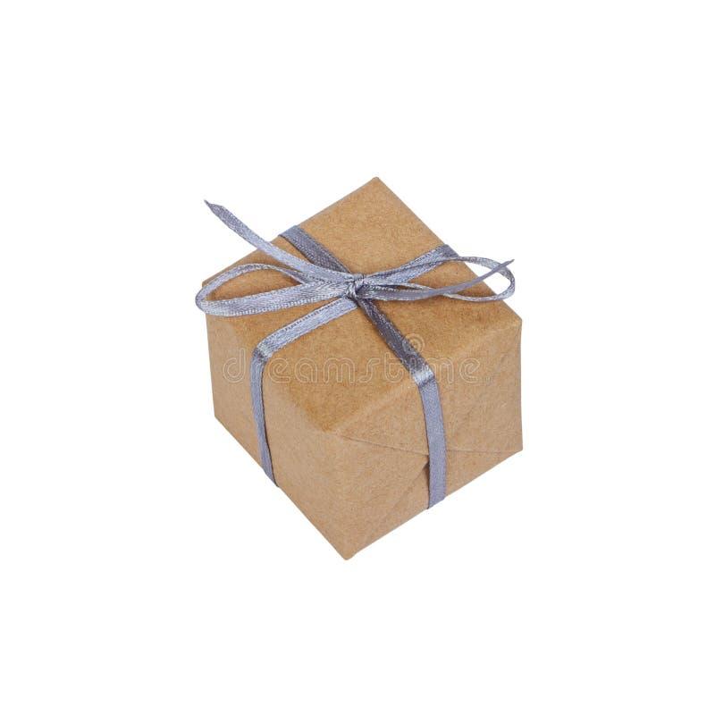 在褐色包裹的礼物盒回收了在白色背景有银色丝带顶视图隔绝的纸,包括的裁减路线 库存照片
