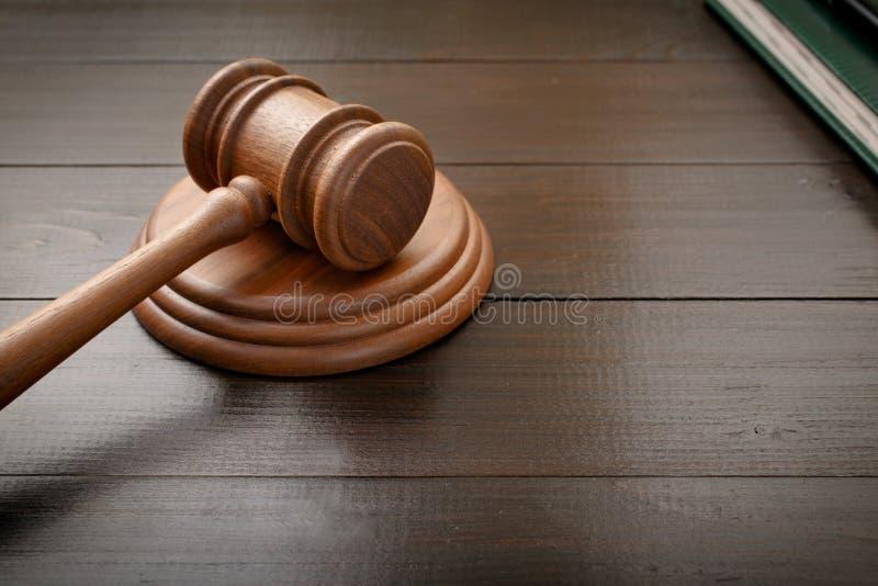 在褐色被上漆的木书桌上的法官锤子 免版税库存照片