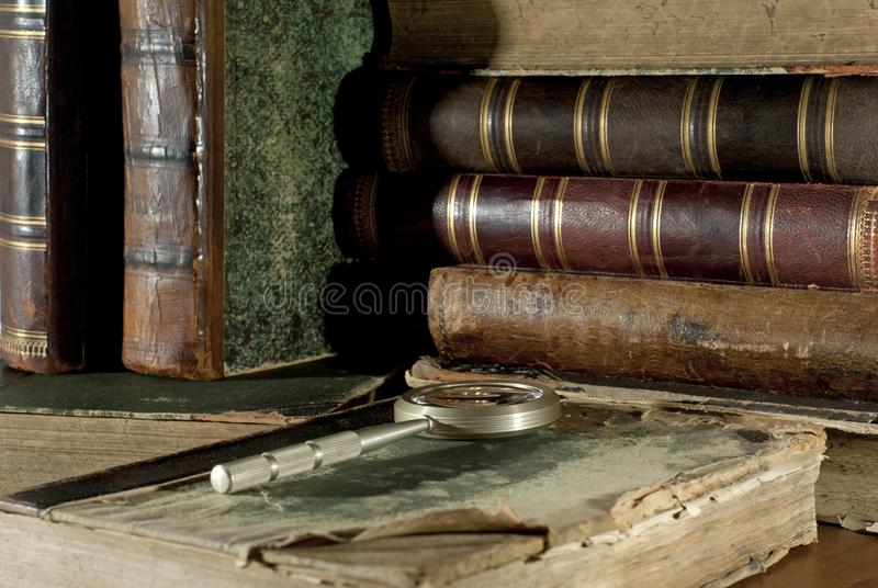 在褴褛盖子和一个放大镜的一本古色古香的书在其他旧书被弄脏的背景  免版税库存照片