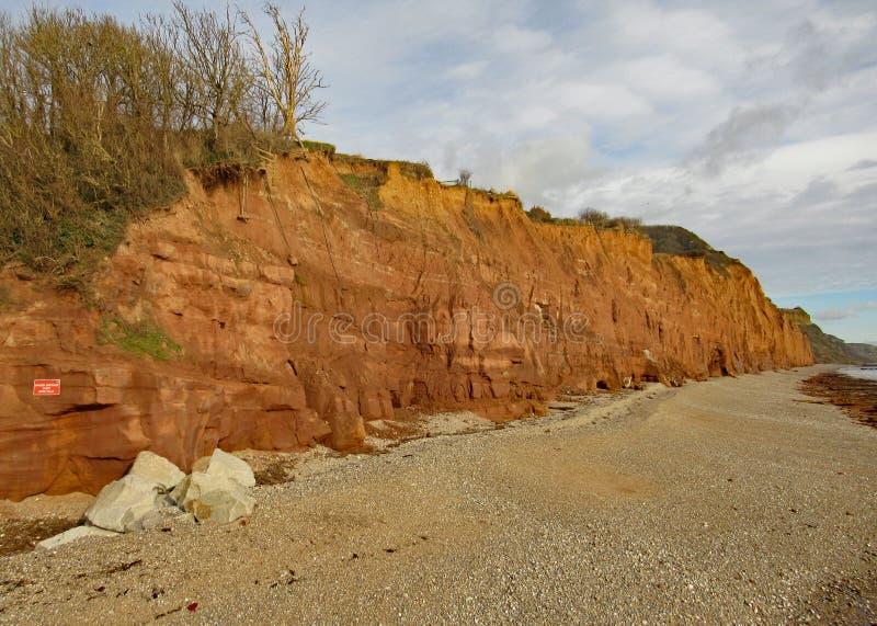 在西德茅斯的木瓦海滩在有侏罗纪海岸的红砂岩峭壁的德文郡在背景中 免版税库存图片