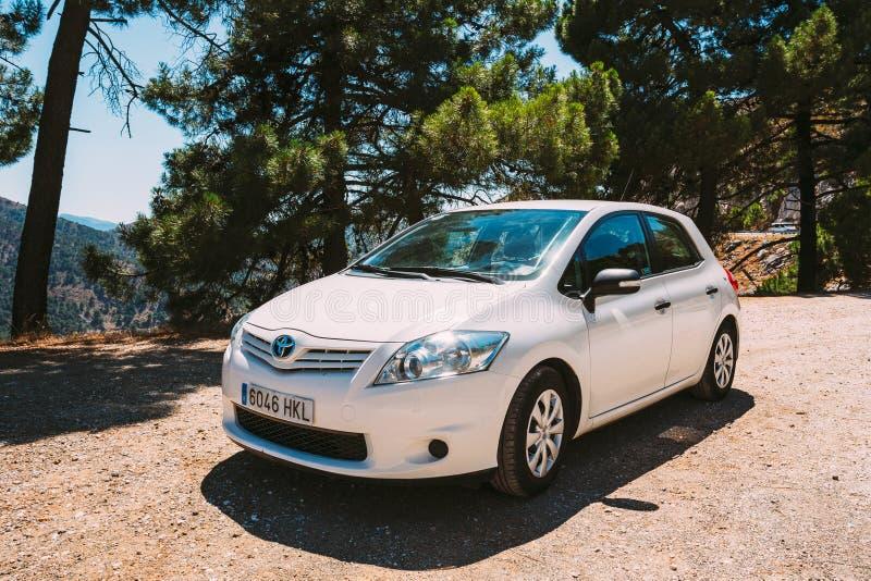 在西班牙自然风景的白色颜色丰田Auris汽车 图库摄影