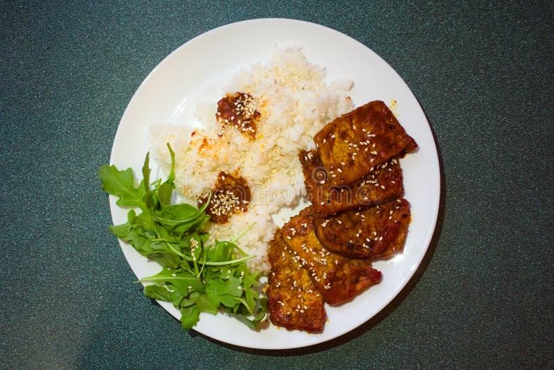 在西红柿酱机智香料炖的油煎的大豆肉用煮沸的米 服务在有新鲜的绿色芝麻菜叶子的白色板材 r 库存图片