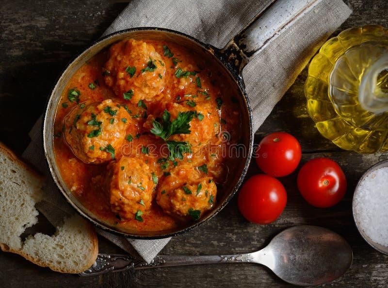 在西红柿酱的丸子在平底锅、面包和蕃茄在木背景 库存照片