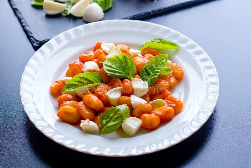 在西红柿酱的尼奥基alla Sorrentina与绿色新鲜的蓬蒿和无盐干酪球在板材服务 免版税库存图片