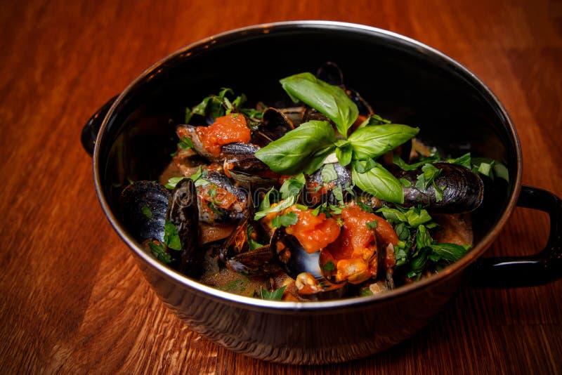 在西红柿酱的比利时煮沸的淡菜用在服务的金属碗的新鲜的荷兰芹 免版税库存照片