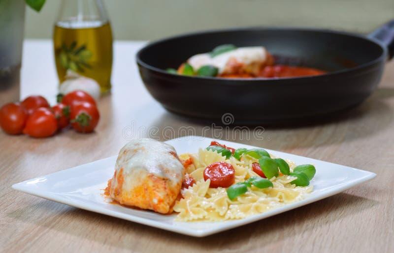 在西红柿酱的Farfalle面团与鸡,在板材的蓬蒿 库存图片