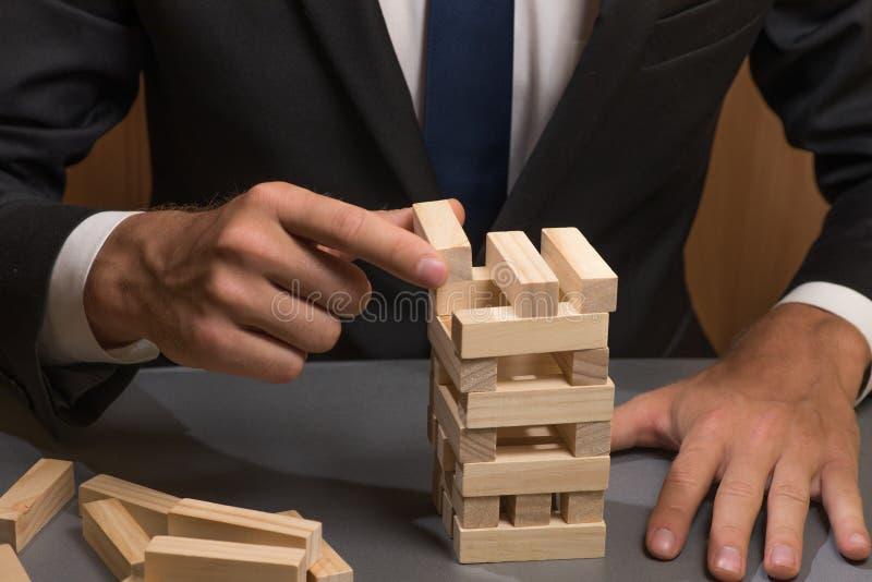 在西装的商人建造木块塔  免版税图库摄影