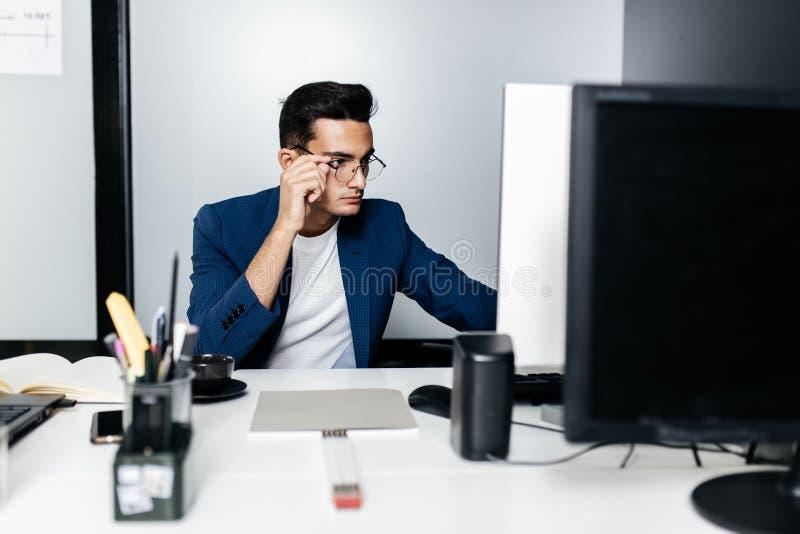 在西装穿戴的玻璃的年轻人建筑师坐在一台计算机前面的一张书桌在办公室 免版税库存图片