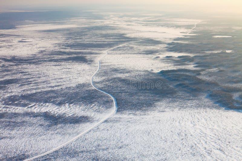 在西西伯利亚,顶视图的冻沼泽的冬天路 库存照片