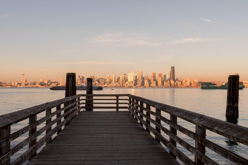 在西雅图海湾的码头与在街市摩天大楼在背景中,华盛顿,美国的日落光 库存照片