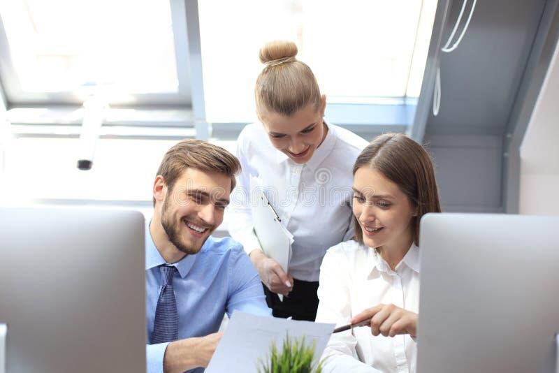 在见面的起始的企业队在现代明亮的办公室内部激发灵感,研究片剂和个人计算机计算机 免版税库存照片