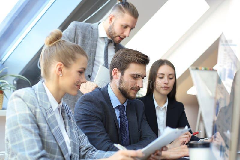 在见面的起始的企业队在现代明亮的办公室内部激发灵感,研究片剂和个人计算机计算机 免版税库存图片