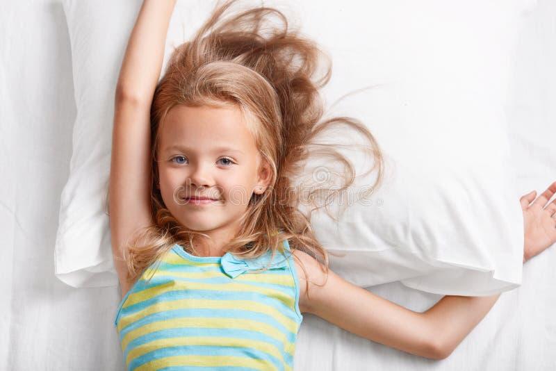 在观点的可爱的轻的头发的小孩子上,在床上有蓝眼睛,舒展,在白色枕头的谎言,穿戴在五颜六色的str 免版税库存照片