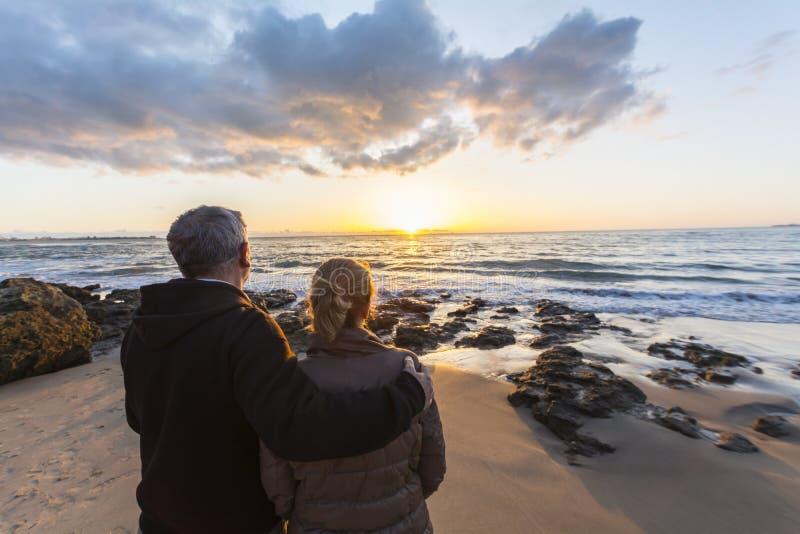 在观看在海滩的爱的夫妇日落 库存图片