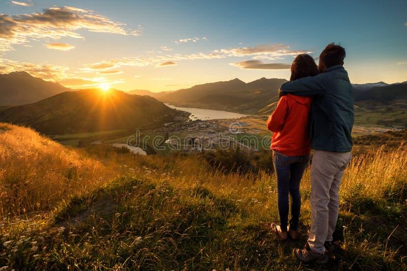 在观看日落的年轻恋人的爱图象的夫妇在山顶部 库存图片